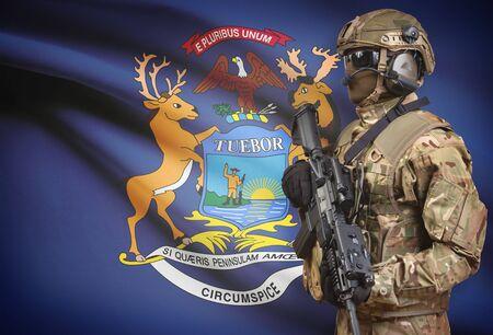 Soldier in helmet holding machine gun with USA state flag on background - Michigan