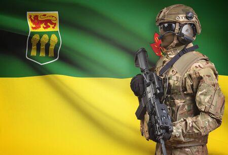 saskatchewan flag: Soldier in helmet holding machine gun with Canadian province flag on background - Saskatchewan