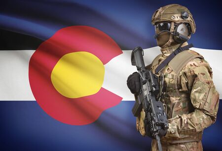 on duty: Soldier in helmet holding machine gun with USA state flag on background - Colorado Stock Photo