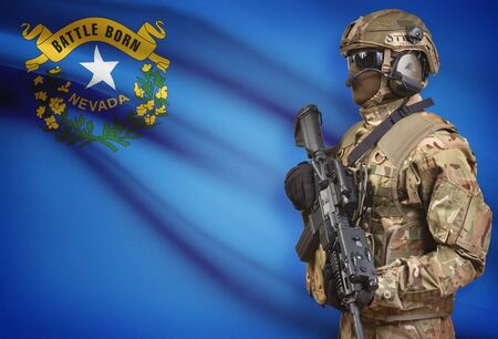 troop: Soldier in helmet holding machine gun with USA state flag on background - Nevada Stock Photo