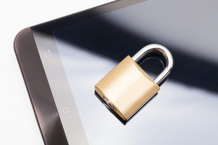 Small lock over a smartphone. Mobile phone security and data protection concept Stock Photo