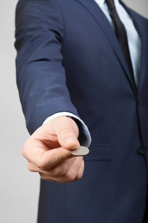25 cents: Businessman in suit holding 25 US cents in hand
