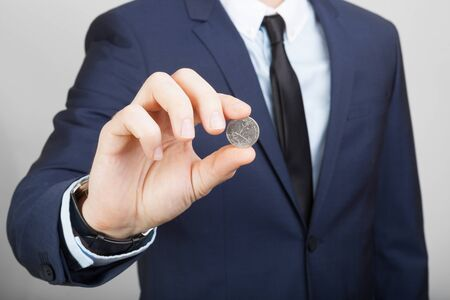 25 cents: Businessman in neat suit holding 25 US cents coin in hand Stock Photo