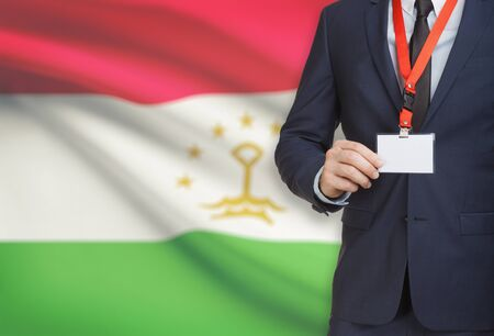 Businessman holding name card badge on a lanyard with a flag on background - Tajikistan