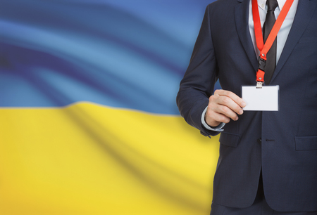 Businessman holding name card badge on a lanyard with a flag on background - Ukraine