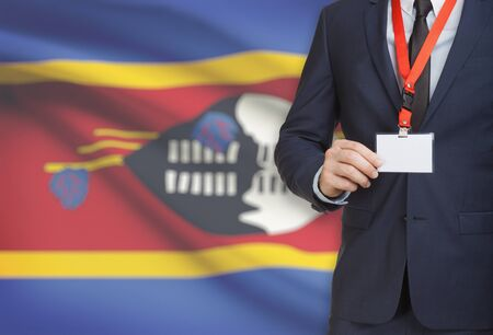 Businessman holding name card badge on a lanyard with a flag on background - Swaziland