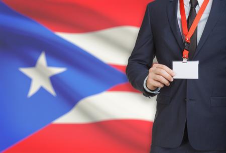 bandera de puerto rico: Businessman holding name card badge on a lanyard with a flag on background - Puerto Rico