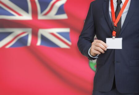 Businessman holding name card badge on a lanyard with a flag on background - Bermuda Stock Photo