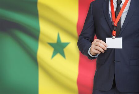Businessman holding name card badge on a lanyard with a flag on background - Senegal