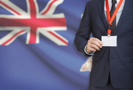 Businessman holding name card badge on a lanyard with a flag on background - Falkland Islands