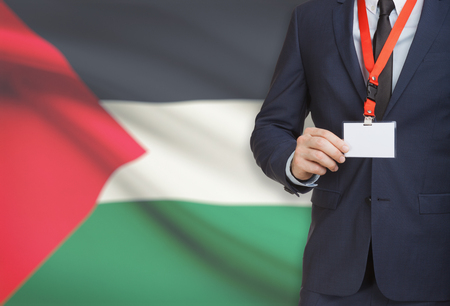 Businessman holding name card badge on a lanyard with a flag on background - Palestine