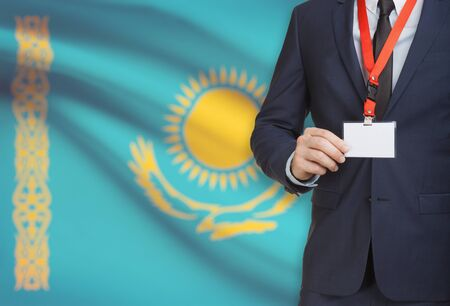 Businessman holding name card badge on a lanyard with a flag on background - Kazakhstan