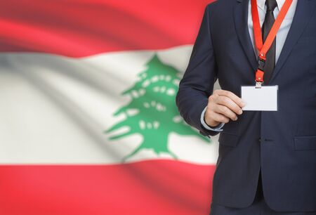 Businessman holding name card badge on a lanyard with a flag on background - Lebanon