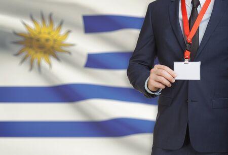 bandera de uruguay: Businessman holding name card badge on a lanyard with a flag on background - Uruguay Foto de archivo