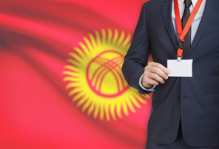 Businessman holding name card badge on a lanyard with a flag on background - Kyrgyzstan