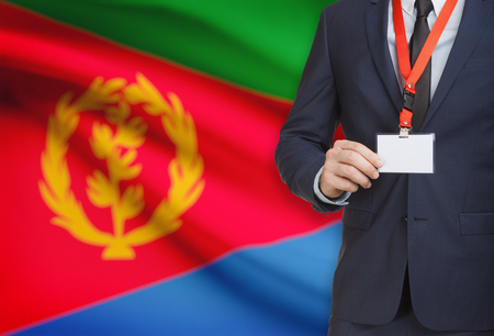 Businessman holding name card badge on a lanyard with a flag on background - Eritrea Stock Photo