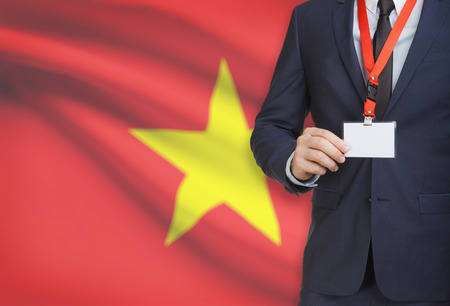 Businessman holding name card badge on a lanyard with a flag on background - Vietnam Stock Photo
