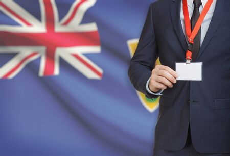Businessman holding name card badge on a lanyard with a flag on background - Turks and Caicos Islands