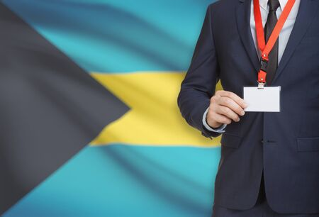 Businessman holding name card badge on a lanyard with a flag on background - Bahamas Stock Photo