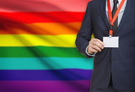 Businessman holding name card badge on a lanyard with a flag on background - LGBT