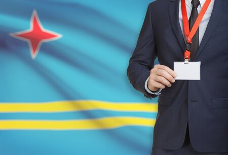 Businessman holding name card badge on a lanyard with a flag on background - Aruba Stock Photo