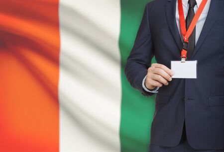Businessman holding name card badge on a lanyard with a flag on background - Ivory Coast
