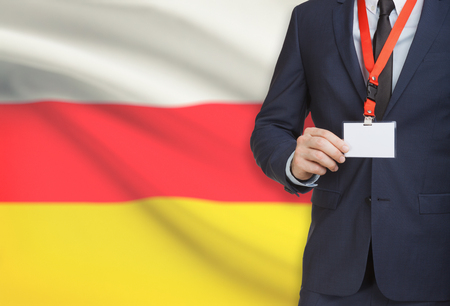 Businessman holding name card badge on a lanyard with a flag on background - South Ossetia