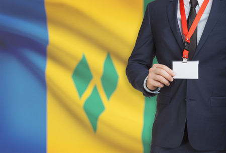 Businessman holding name card badge on a lanyard with a flag on background - Saint Vincent and the Grenadines