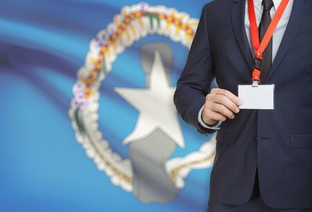 Businessman holding name card badge on a lanyard with a flag on background - Northern Mariana Islands Stock Photo