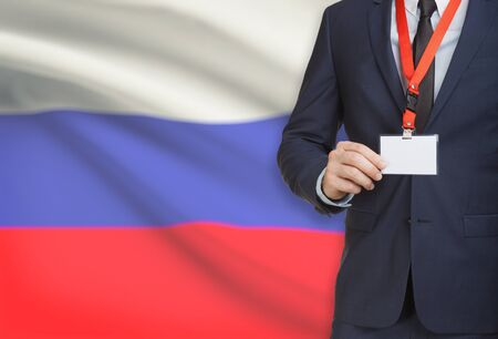 Businessman holding name card badge on a lanyard with a flag on background - Russia