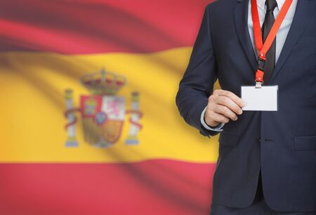 Businessman holding name card badge on a lanyard with a flag on background - Spain