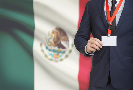 Businessman holding name card badge on a lanyard with a flag on background - Mexico
