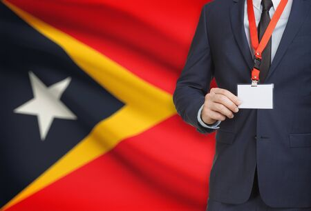 Businessman holding name card badge on a lanyard with a flag on background - East Timor