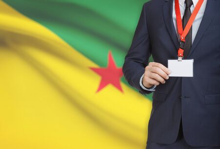 Businessman holding name card badge on a lanyard with a flag on background - French Guiana