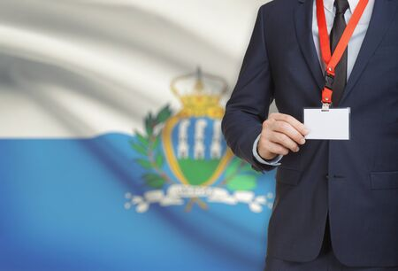 Businessman holding name card badge on a lanyard with a flag on background - San Marino