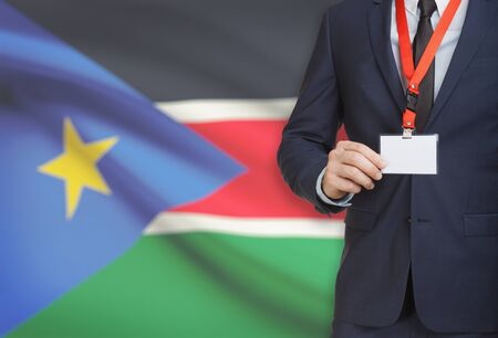 Businessman holding name card badge on a lanyard with a flag on background - South Sudan