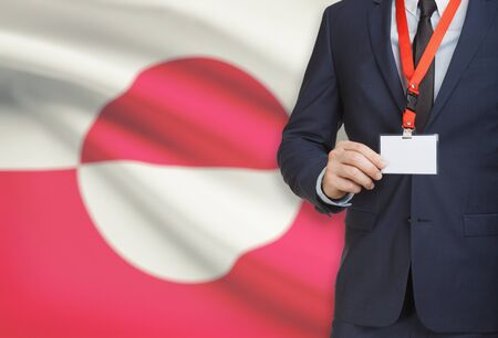 greenlandic: Businessman holding name card badge on a lanyard with a flag on background - Greenland