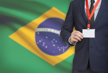 Businessman holding name card badge on a lanyard with a flag on background - Brazil