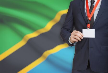 Businessman holding name card badge on a lanyard with a flag on background - Tanzania Stock Photo