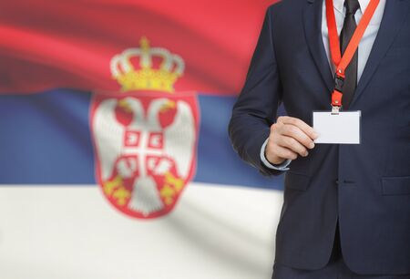 Businessman holding name card badge on a lanyard with a flag on background - Serbia