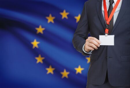 Businessman holding name card badge on a lanyard with a flag on background - European Union