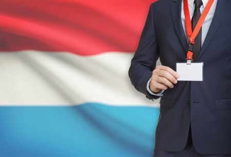 Businessman holding name card badge on a lanyard with a flag on background - Luxembourg Stock Photo