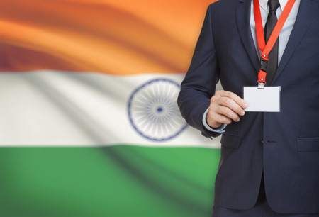 Businessman holding name card badge on a lanyard with a flag on background - India