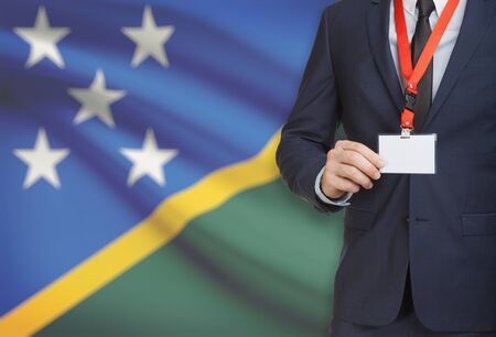 Businessman holding name card badge on a lanyard with a flag on background - Solomon Islands