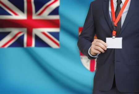 Businessman holding name card badge on a lanyard with a flag on background - Fiji Stock Photo