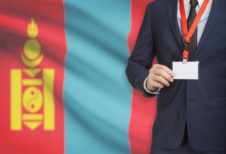 Businessman holding name card badge on a lanyard with a flag on background - Mongolia Stock Photo