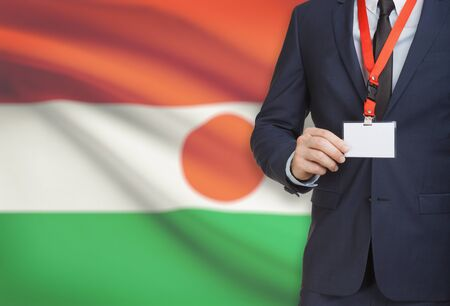 Businessman holding name card badge on a lanyard with a flag on background - Niger Stock Photo