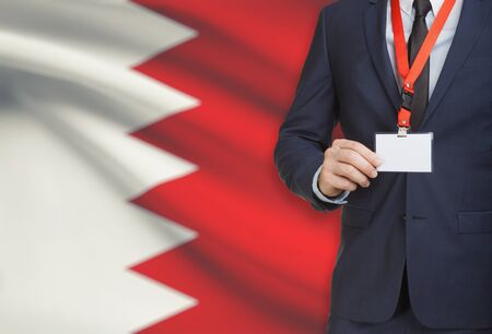 Businessman holding name card badge on a lanyard with a flag on background - Bahrain