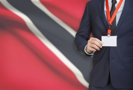 Businessman holding name card badge on a lanyard with a flag on background - Trinidad and Tobago Stock Photo