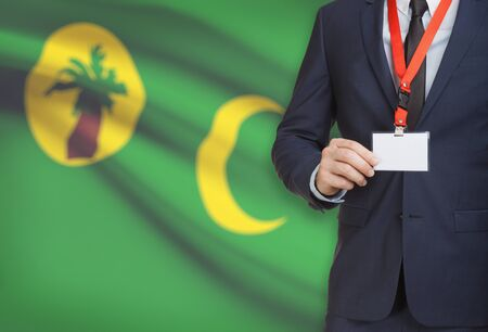 Businessman holding name card badge on a lanyard with a flag on background - Cocos (Keeling) Islands